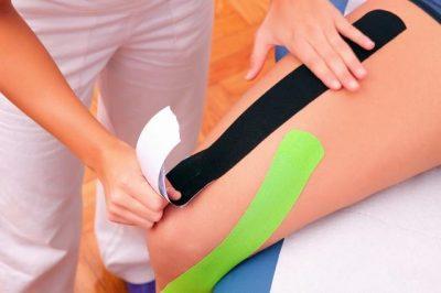 Practioner applying kinesiotape to athlete.